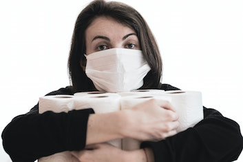 A woman in a medical face mask with armfuls of toilet paper rolls