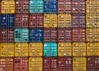 Yellow, red, orange and blue shipping containers stacked on top and beside each other