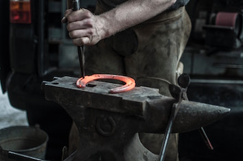 A red-hot metal horseshoe on a blacksmith's anvil